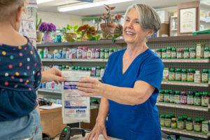 compounding pharmacy oak island nc, image of staff providing a customer their pharmacy order