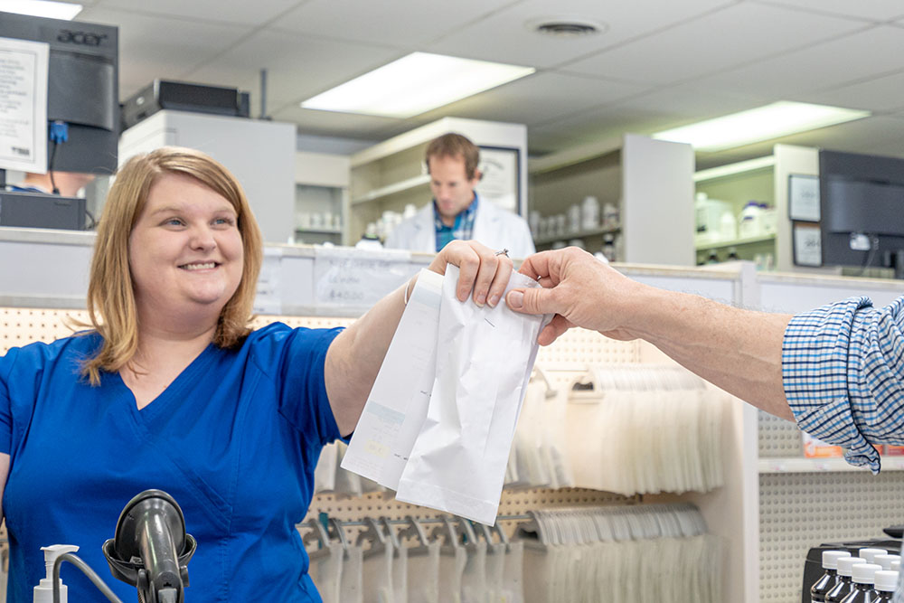 shallotte pharmacist, image of staff handing an order to a customer